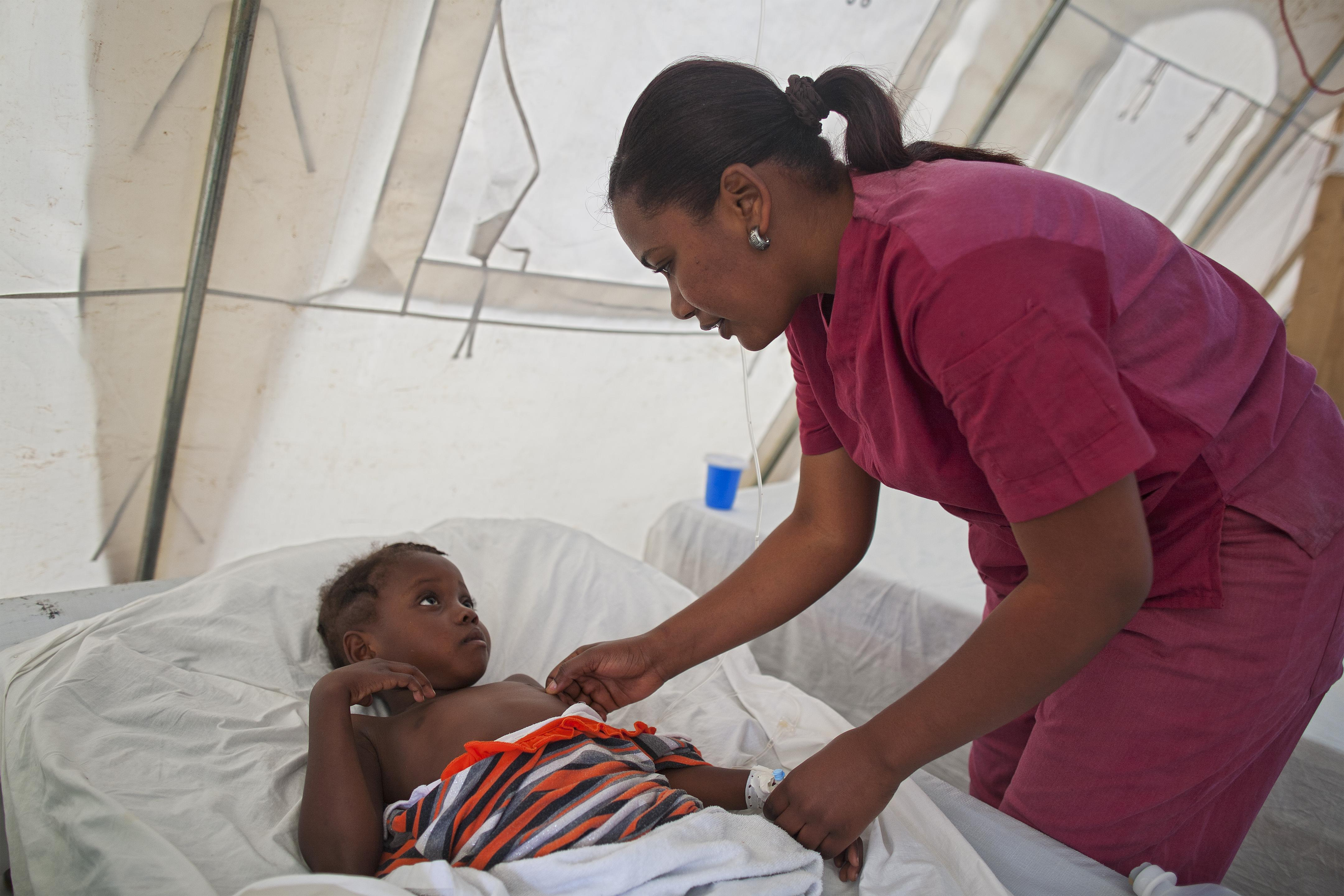 Rose Luzette Charles, a nurse at a Cholera Treatment Center, checks on Widelene Philistin, 7, who is recovering from cholera. Photo credits: ECHO/Care/Evelyn Hockstein