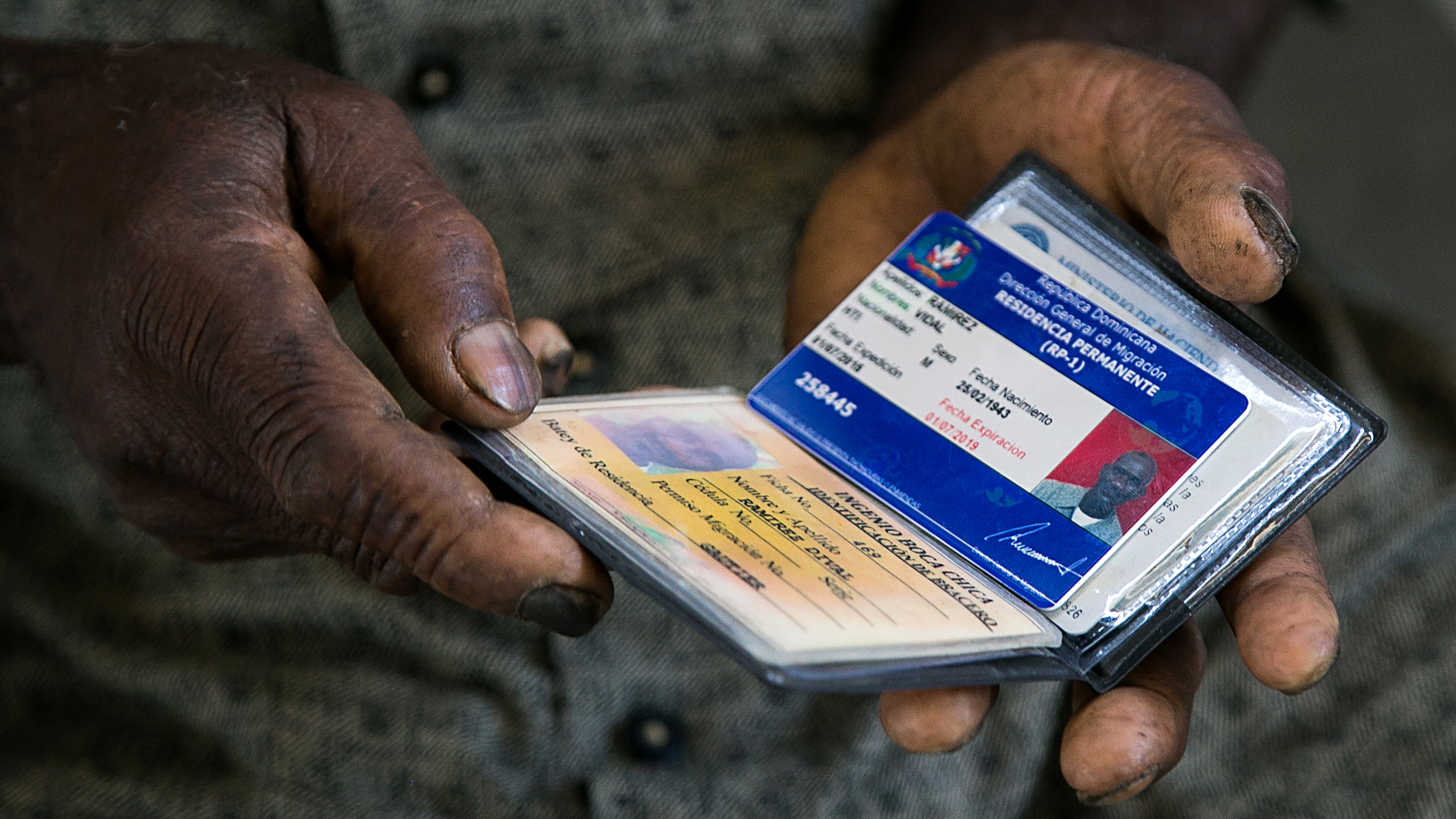 Man shows Permanent Resident Card in Dominican Republic. Photo Credit: PresidenciaRD